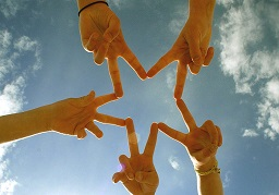 people joining hands to make a star shape