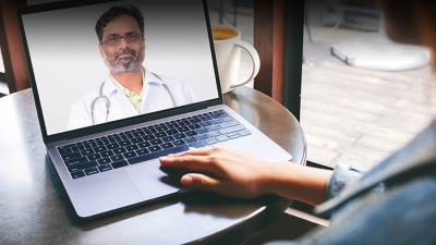 Person having a video visit with a doctor on a laptop screen
