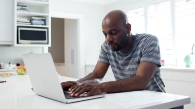 Man typing on his laptop at home