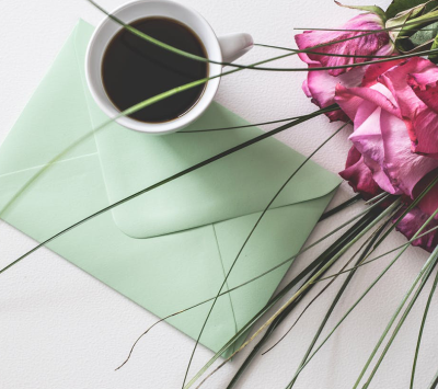 flowers and card on the table with a cup of coffee