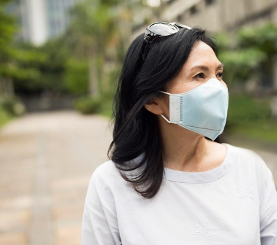 Middle aged Asian woman wearing protective mask.