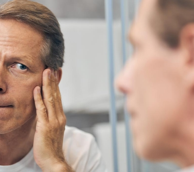 Middle aged man examining his face on mirror.