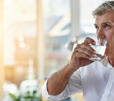 Mature man drinking water.