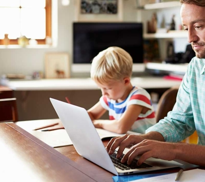 Father using laptop with young son next to him.
