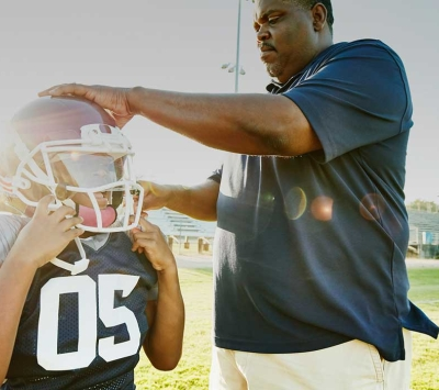 Youth football player's parent help with helmet