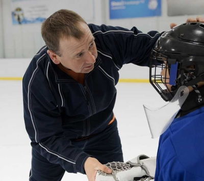 Coach evaluating youth hockey player