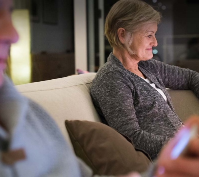 Mature couple reading on devices at home