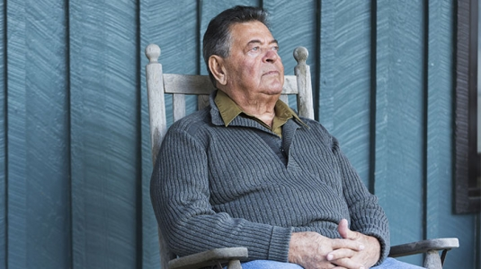 mature man sitting on outdoor chair