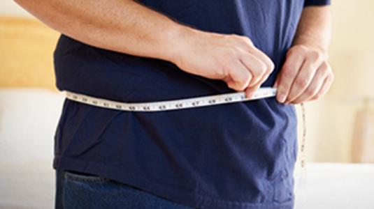 person holding measuring tape around waist