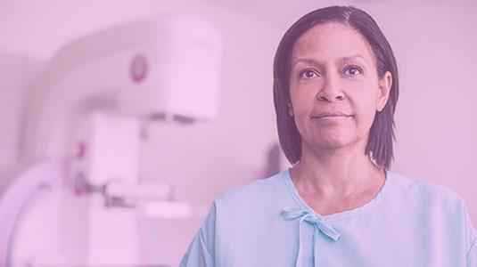 Female patient standing front of mammogram machine