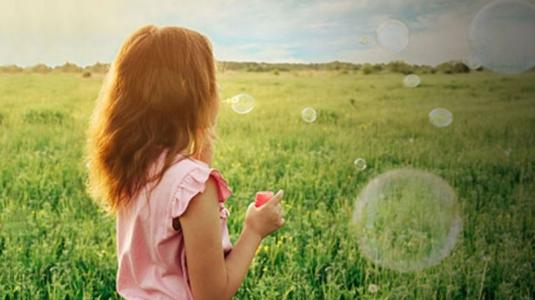 Girl blowing bubbles in field.
