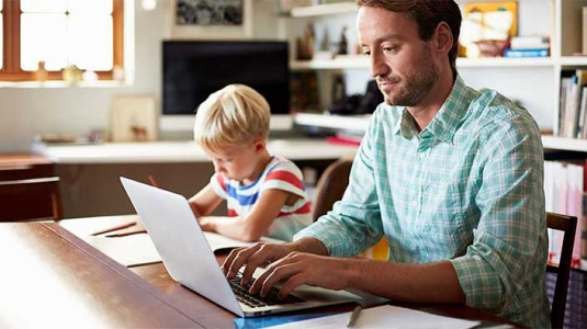 Dad using laptop next to young son.