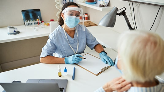 Masked Female patient and healthcare worker at medical office