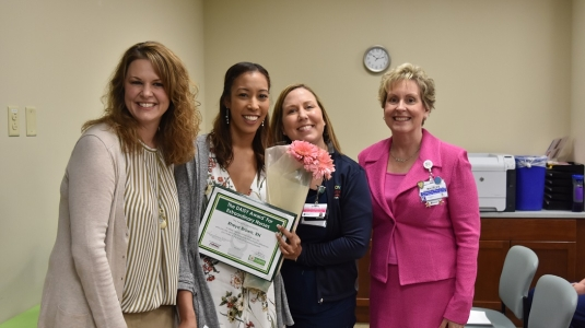 four nurses smiling