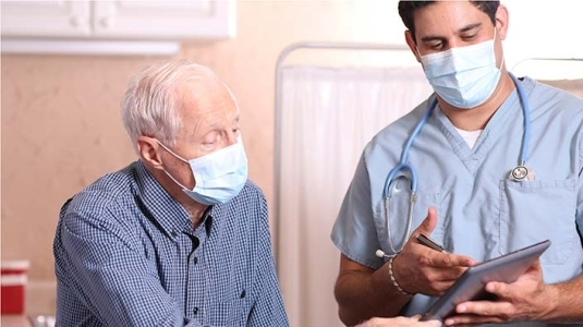 masked patient and doctor having a consult